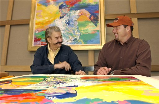 """Leroy Neiman talks to then-New York Yankees pitcher Roger Clemens while signing limited edition serigraphs based on Neiman's painting """"The Rocket,"""" of Clemens on the mound in pinstripes in this Nov. 13, 2003, photo."""