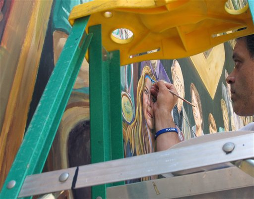 Artist Michael Pilato paints a blue ribbon on his mural in State College, Pa., on Monday.