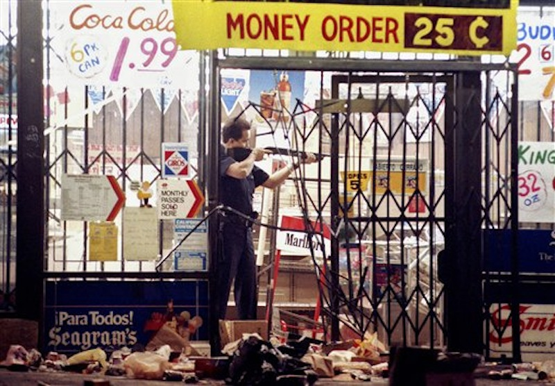 In this April 30, 1992 file photo, a Los Angeles police officer takes aim at a looter in a market at Alvarado and Beverly Boulevard in Los Angeles during the second night of rioting in the city. Rodney King, the black motorist whose 1991 videotaped beating by Los Angeles police officers was the touchstone for one of the most destructive race riots in the nation's history, has died, his publicist said Sunday, June 17, 2012. He was 47. (AP Photo/John Gaps III, File)