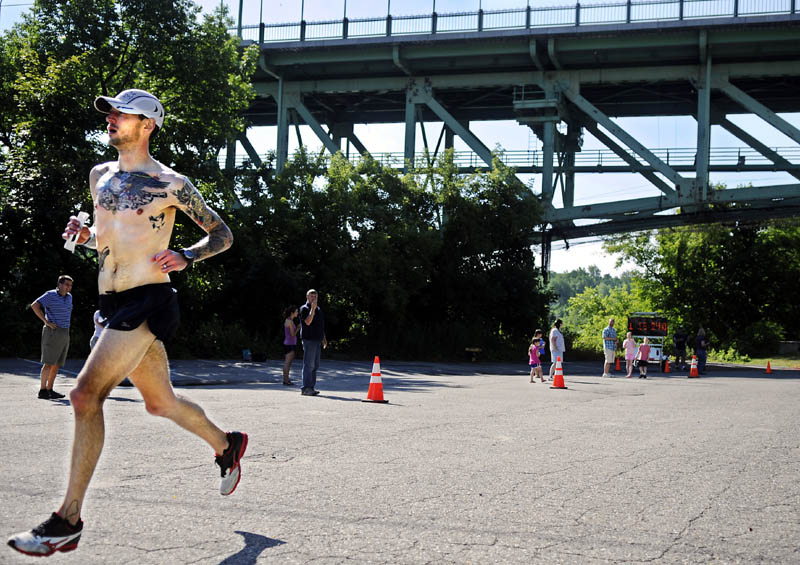 FIRST TO THE LINE: Seth Hasty runs beneath Memorial Bridge in Augusta to finish first in the Kennebec River Rail Trail Half Marathon on Sunday.