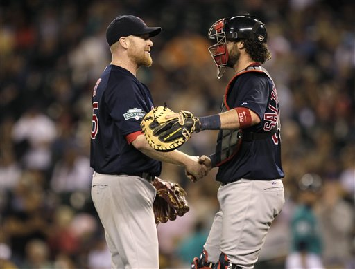 Boston Red Sox starting pitcher Aaron Cook, left, greets catcher Jarrod Saltalamacchia, right, after Cook threw a two-hit shutout against the Seattle Mariners in a baseball game, Friday, June 29, 2012, in Seattle. The Red Sox beat the Mariners 5-0. (AP Photo/Ted S. Warren)