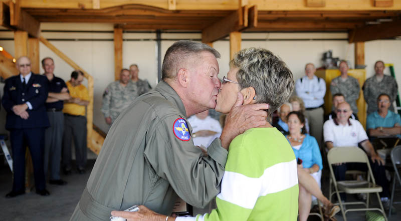 Eugene Richardson kisses his wife, Pam, on Monday after he was recognized for 50 years of safe aviation at the Civil Air Patrol hangar in Augusta.