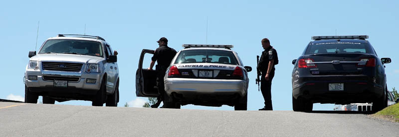 AT THE SCENE: Police officers stand in the parking lot next Kennebec Valley Council of Governments building in Fairfield after the Rite Aid on Main Street was robbed Friday.
