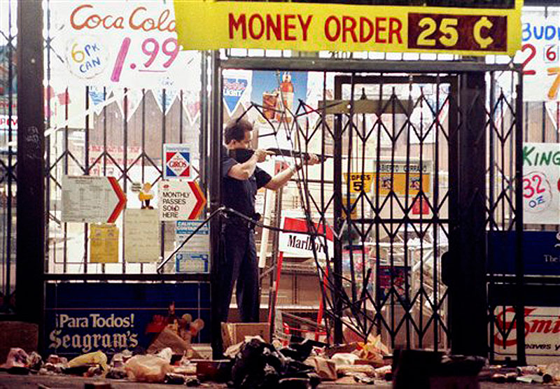 In this April 30, 1992 file photo, a Los Angeles police officer takes aim at a looter in a market at Alvarado and Beverly Boulevard in Los Angeles during the second night of rioting in the city. Rodney King, the black motorist whose 1991 videotaped beating by Los Angeles police officers was the touchstone for one of the most destructive race riots in the nation's history, has died, his publicist said Sunday, June 17, 2012. He was 47.(AP Photo/John Gaps III, File)