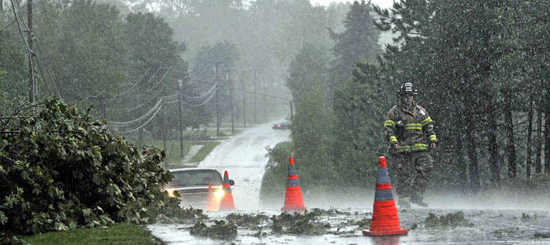 A Fairfield firefighter sets up cones to redirect motorists around downed power lines and tree limbs from a powerful storm that rolled through central Maine on Friday afternoon.