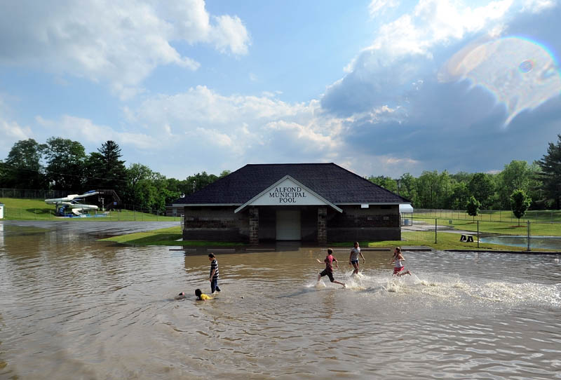 Staff Photo by Michael G. Seamans Children runs through the flooded parking lot at the Alfond Municipal Pool on North Street as a powerful storm rolled through Waterville Friday afternoon.