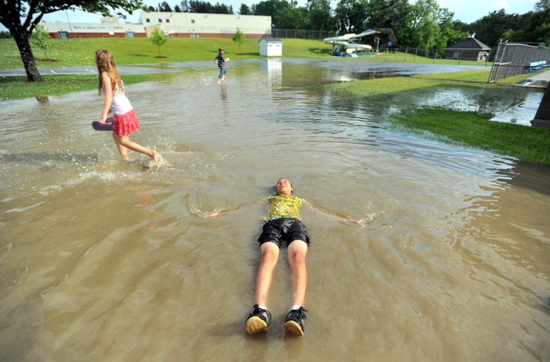 Staff Photo by Michael G. Seamans Zack Taylor, 13, floats on his back in the flooded parking lot at the Alfond Municipal Pool on North Street in Waterville Friday.