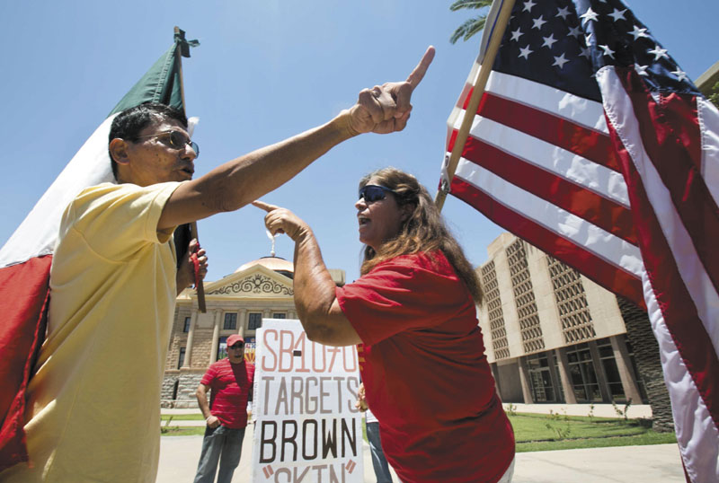 Andy Hernandez, carrying a Mexican flag, and Allison Culver, carrying an American flag argue Monday about SB1070 outside the State Capitol Building in Phoenix. While finding much of the Arizona law unconstitutional, the U.S. Supreme Court said Monday that one part would stand -- the portion requiring police to check the status of someone they suspect is not in the United States legally. SB1070