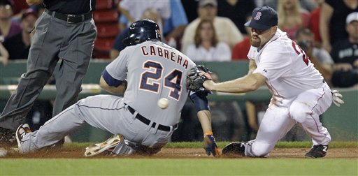 Boston Red Sox third baseman Kevin Youkilis applies a tag without the ball as Detroit Tigers' Miguel Cabrera advances to third on a throwing error, after stealing second base during the ninth inning of a baseball game at Fenway Park in Boston, Thursday, May 31, 2012. (AP Photo/Charles Krupa)