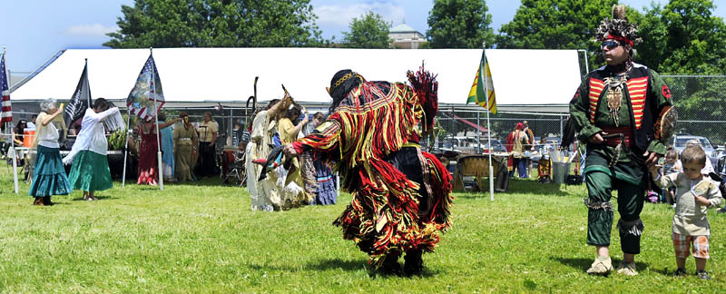 People clad in American Indian regalia dance together Sunday during the Honoring Our Veterans Powwow at Togus.