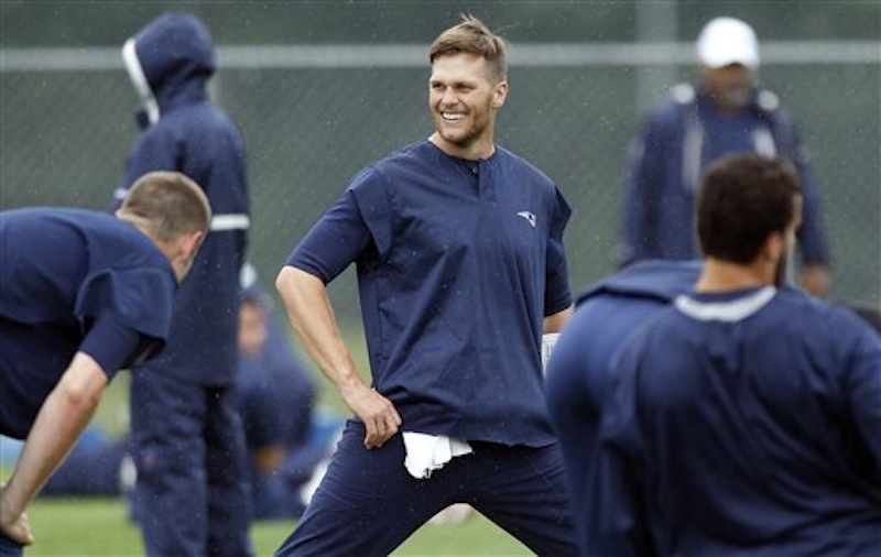 New England Patriots quarterback Tom Brady smiles while stretching during NFL football practice in Foxborough, Mass., Wednesday, June 13, 2012. (AP Photo/Charles Krupa)