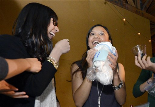 Jessica Nguyen, right, reacts after smelling a shirt as Angela Abad-Santos looks on during a pheromone party in Los Angeles
