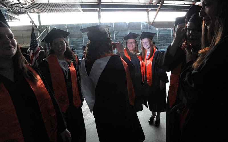 Staff Photo by Michael G. Seamans Brittni Martell,left center, and Maddie Daily, right, center are illuminated by a camera flash asWinslow High School's class of 2012 prepare for commencement ceremonies in Alfond Rink prio to the ceremonies in Wadsworth Gymnasium at Colby College in Waterville on Wednesday.