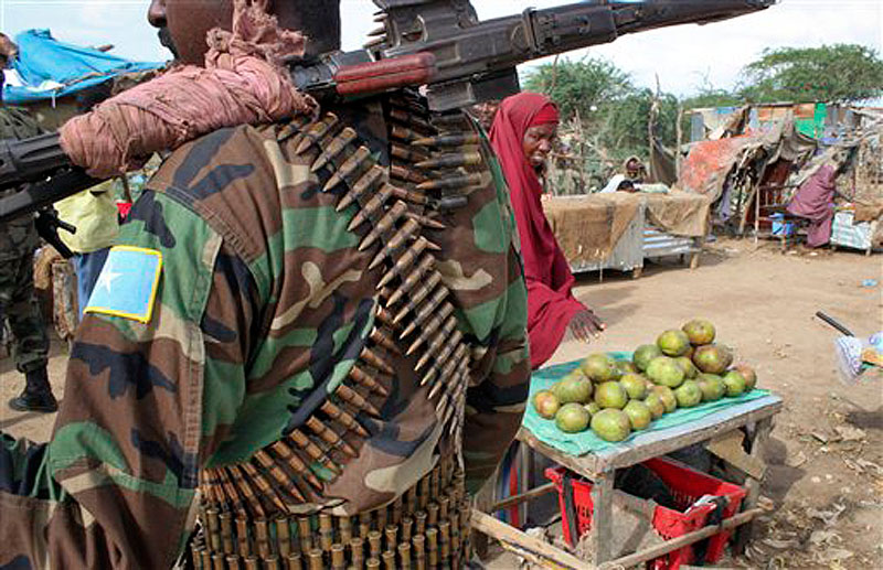 In this photo taken Thursday, June 7, 2012, a fruit seller looks across as a Somali government soldier stands guard in Afgoye, west of the capital Mogadishu, in Somalia. The seaside Somali capital is enjoying a peace that, except for the infrequent attack, has lasted the better part of a year and Somalis who fled decades of war are coming back, as are U.N. workers who long operated out of Nairobi, the capital of neighboring Kenya. (AP Photo/Jason Straziuso)