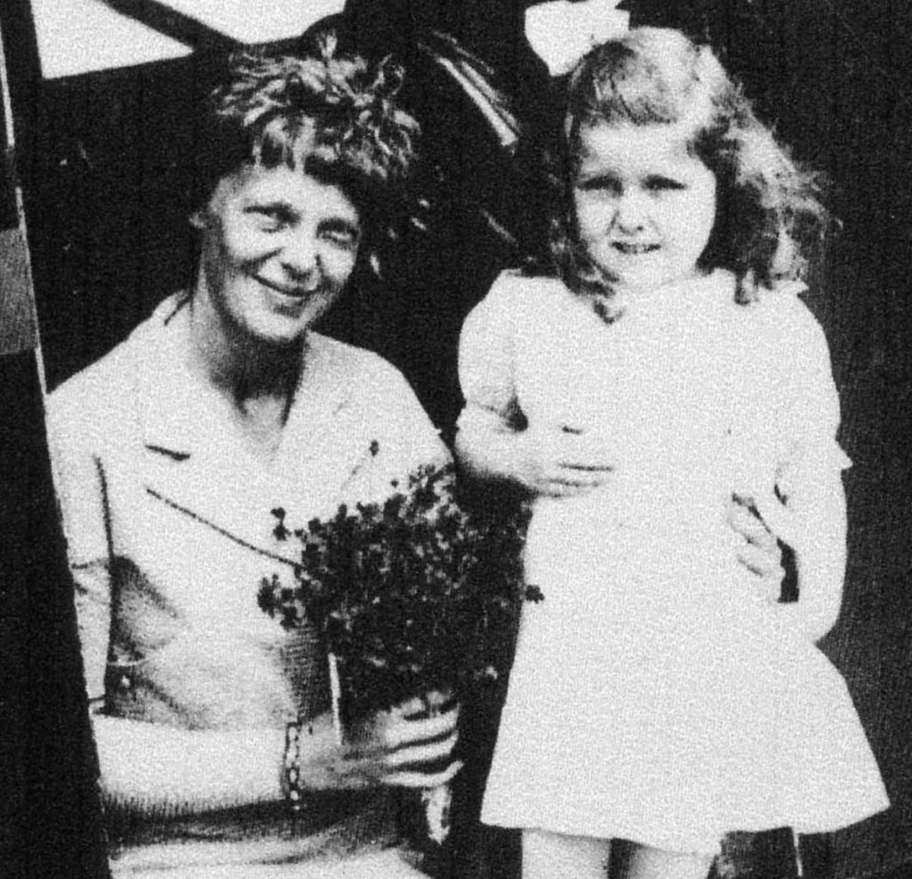 Amelia Earhart receives flowers from 5-year old Gladys Chase, of Augusta, on Aug. 14, 1934, at the Augusta airport. The two were photographed in the doorway of a Boston & Maine Airways Stinson SM-6000B passenger plane.