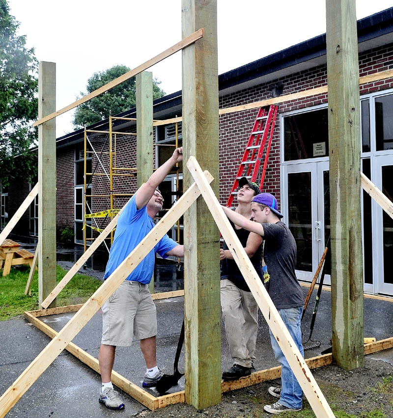 UP AND AWAY: Instructor Jim Easler, left, helps Carrabec High School students Kenneth White, center, and Anthony Toneatti build a portico entry structure in front of the North Anson school on Tuesday.