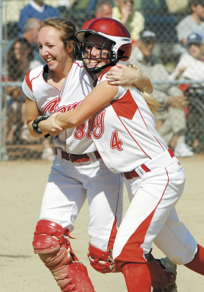 LET ME HELP: Cony's Nicole Rugan, left, hugs Alyssa Brochu after Brochu scored the Rams' second run in the fourth inning in the Class A softball state championship game Saturday at St. Joseph's College in Standish.
