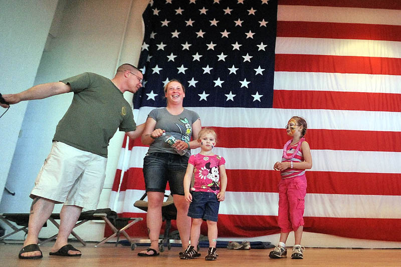 """PARTY: First Sgt. Michael Peacock, left, leads people in singing """"Happy Birthday"""" to Spc. Charilyn Campbell, center left, with her nieces Ayla Nash, 3, center, and Aubriana Nash, 8, on Sunday at the Waterville Armory. VFW Post 1285 held its annual summer celebration for soldiers in the Maine Army National Guard's 488th Military Police Company, which will deploy soon to Afghanistan."""
