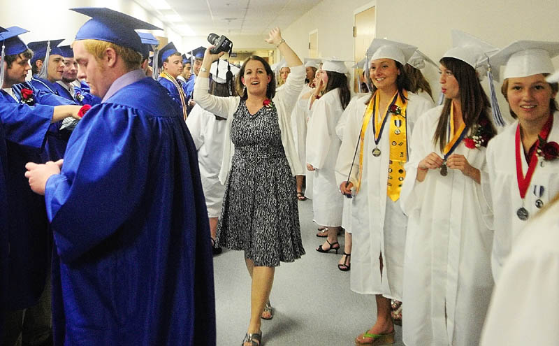 BACK UP: Dee Porter, one of the senior class advisers, tells Erskine Academy graduates to back up in the hallway as they line up before graduation on Friday at the Augusta Civic Center.