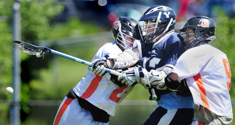 CLIPPER SANDWICH: Yarmouth's William Porter, center, loses the balls as he is doubleteamed by Gardiner's Seth Wing, left, and Dalton Carmichael in an Eastern B semifinal gameon Saturday afternoon in Gardiner.