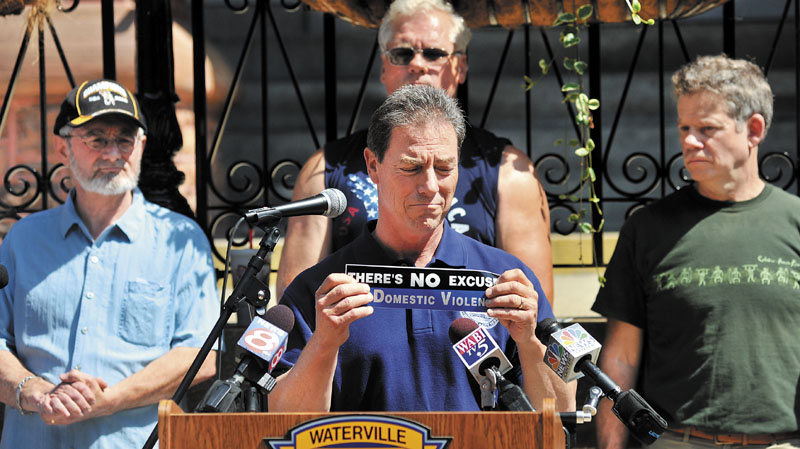 """Waterville City Manager Mike Roy holds a bumper sticker that reads """"There's No Excuse for Domestic Violence"""" as he speaks on the subject of domestic violence during a rally to call on men to take responsibility for creating a community free of domestic violence."""