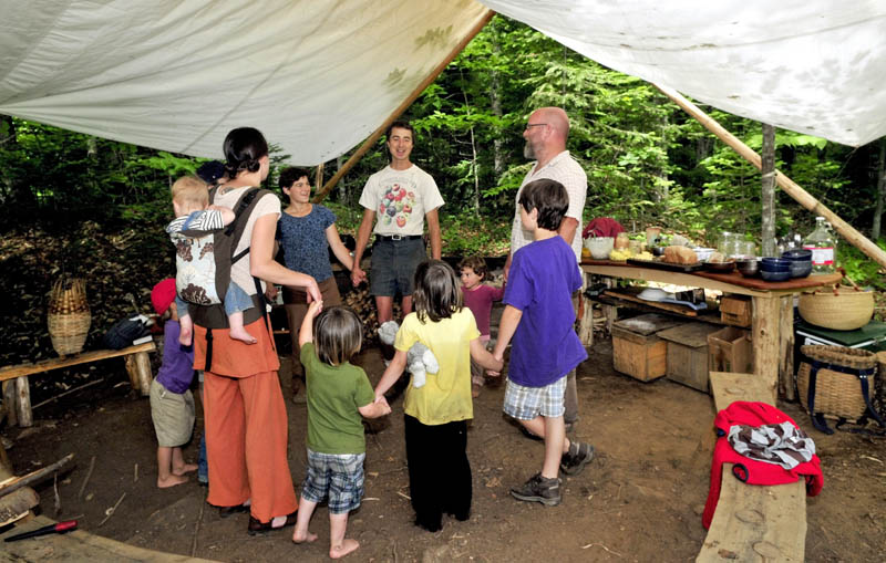 COMMUNAL LUNCH: The host Knapp family and visiting Soule family came together prior to a lunch under a tent at the Koviashuvik School in the woods in Temple on Thursday. Chris Knapp, center, leads the gathering.