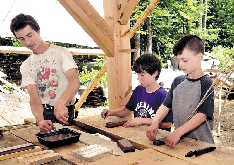PRETTY SHARP: Chris Knapp of the Koviashuvik School in Temple shows Calvin Soule, left, and his brother Ezra how to sharpen knives on Thursday.