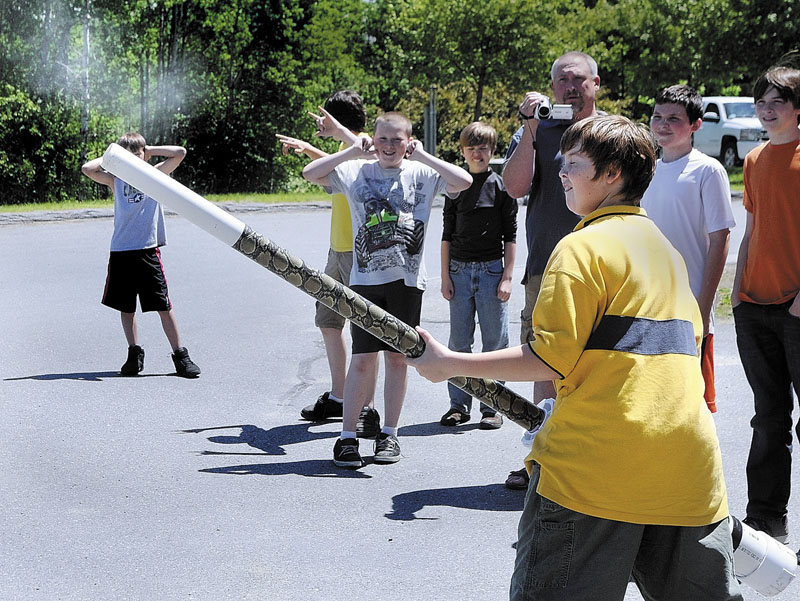 Classmates cover their ears as Robert Shaw fires his potato launcher that he and his father Chris Shaw built for the Ruby Team Science Fair and Invention Convention on Friday at Maranacook Middle School in Readfield. Taylor Anderson and his father Devin Anderson also built a launcher with the Shaws. There were 45 students in 6th, 7th and 8th grades participating in the event.