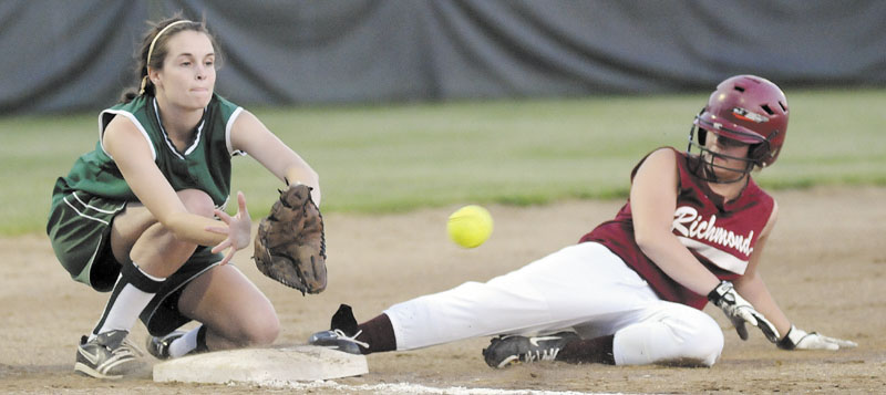 Staff photo by Andy Molloy Richmond High School's Payton Johnson slides into third base ahead of a throw to Rangeley Lakes Regional High School's Emily Carrier during the Western D softball regional final Thursday in Standish.