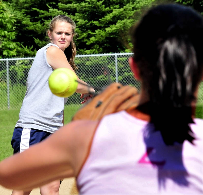 Staff photo by David Leaming Nokomis pitcher Sara Packard throws to player Drew Graves during practice on Monday.