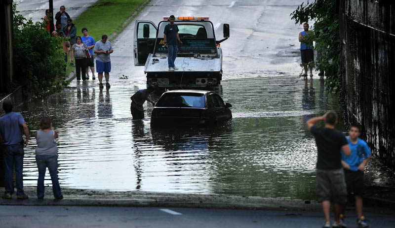 A car on upper Main Street in Fairfield is towed away Friday evening after a fast moving storm blew through the area.