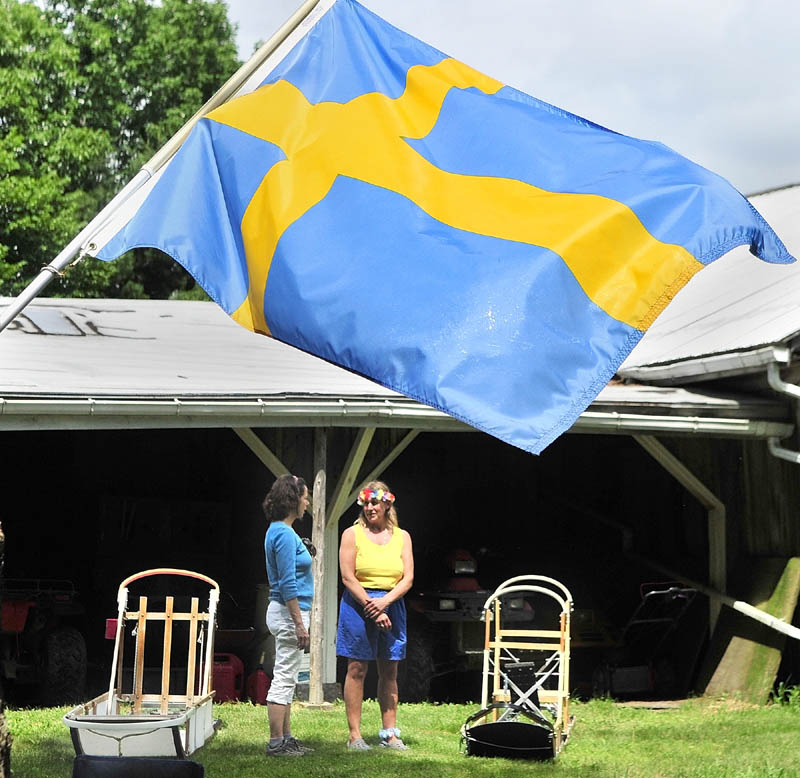A Swedish flag floats in the breeze above Paula Sutton, of Warren, left, and Heywood Kennels co-owner Lindy Howe as they chat beside dog sleds on Saturday in Augusta.