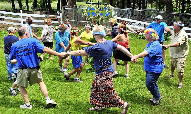 Two rings of people dance in opposite directions around a midsommarstang, or Swedish mid-summer pole, during the the Midsommar Celebration on Saturday at Heywood Kennels in Augusta.