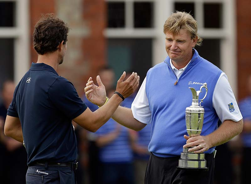 Ernie Els holds the Claret Jug trophy after winning the British Open today, and shakes hands with Adam Scott, who had the lead until bogeying the final four holes at Royal Lytham & St Annes golf club, Lytham St Annes, England.