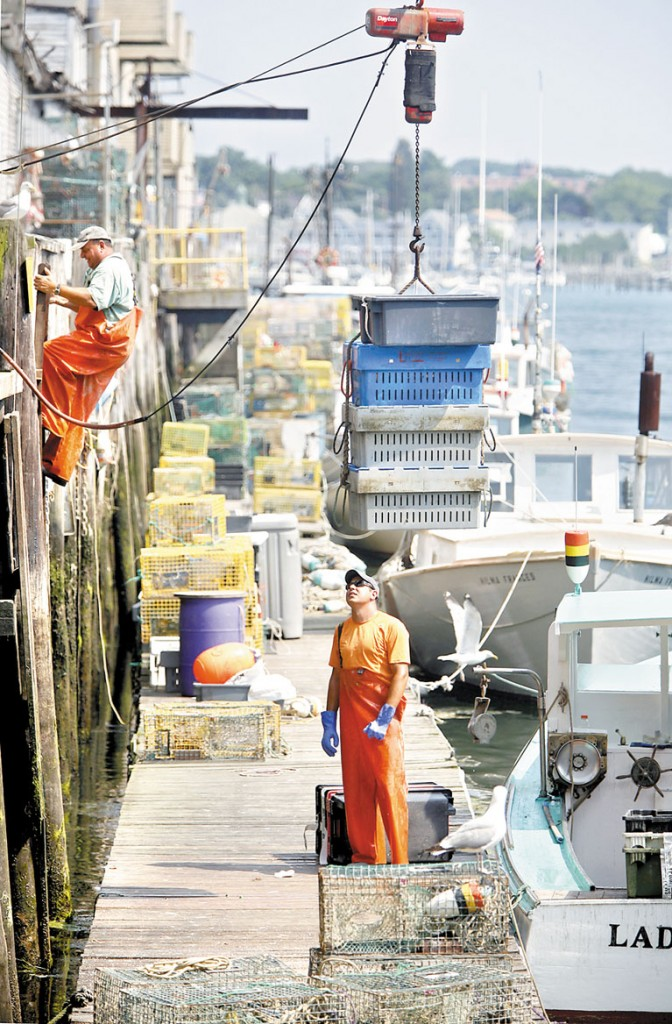 Lobsterman Eric Pray watches as four crates of lobster are lifted from the dock to Harbor Fish Market as his father, Peter, climbs a ladder to the market in Portland on Tuesday.