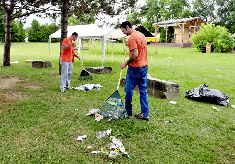 PARTY'S OVER: On Thursday Kennebec County Jail inmates Michael Meader, left, and Ryan Willey rake litter left over from the Winslow Family 4th of July events at Fort Halifax Park in Winslow. The men are participating in a jail community service program.