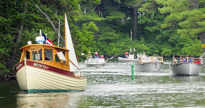 Boats parade down Mill Stream on Wednesday during Independence Day events in Belgrade Lakes village.