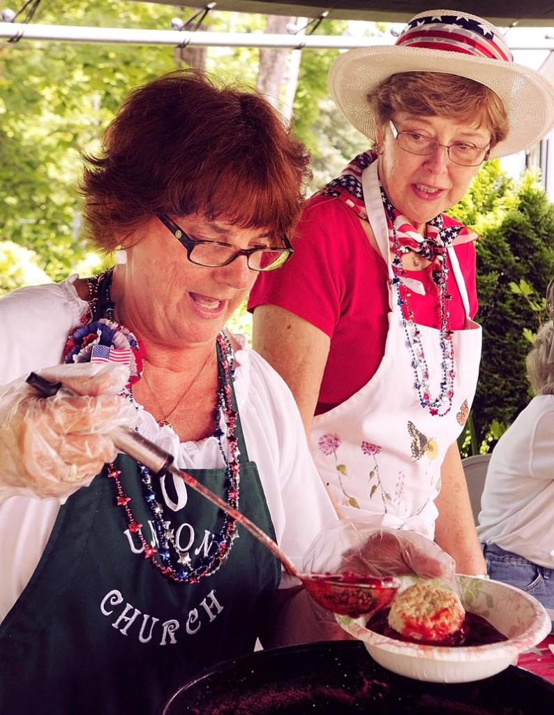 Sharron Burnell, left, and Betty Weaver serve up strawberry shortcakes Wednesday in Belgrade.