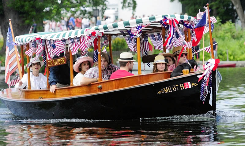 A boat parades down Mill Stream on Wednesday in Belgrade Lakes village.