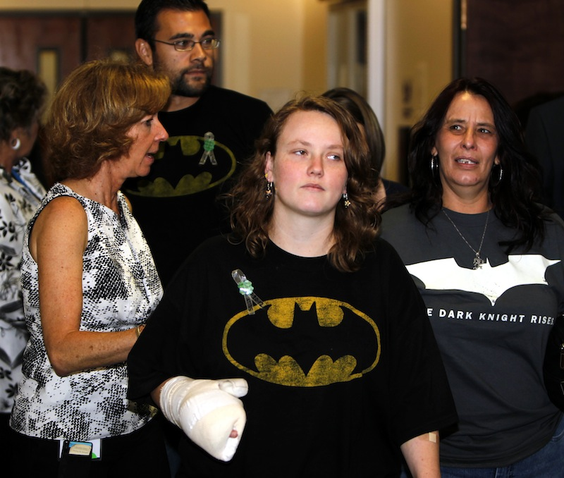Victims are assisted by an advocate, left, as they arrive for an arraignment for suspected theater shooter James Holmes in district court in Centennial, Colo., on Monday, July 30, 2012. Holmes has been charged in the shooting at the Aurora theater on July 20 that killed twelve people and injured more than 50.He is scheduled to appear in court Monday morning. (AP Photo/Ed Andrieski)
