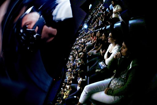 """In this photo taken with a fisheye lens, people watch villain Bane on the screen during the midnight premiere of """"The Dark Knight Rises"""" inside the Liberty Science Center IMAX theater today in Jersey City, N.J."""
