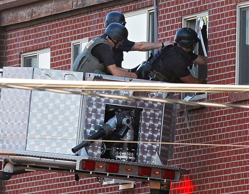 Police use a video camera to look inside the apartment of shooting suspect James Holmes today.