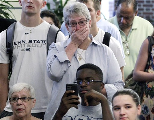 Susan DelPonte, center, of State College, Pa., reacts to a television in the HUB on the Penn State University main campus in State College, Pa., as the NCAA sanctions against the Penn State University football program are announced on Monday.