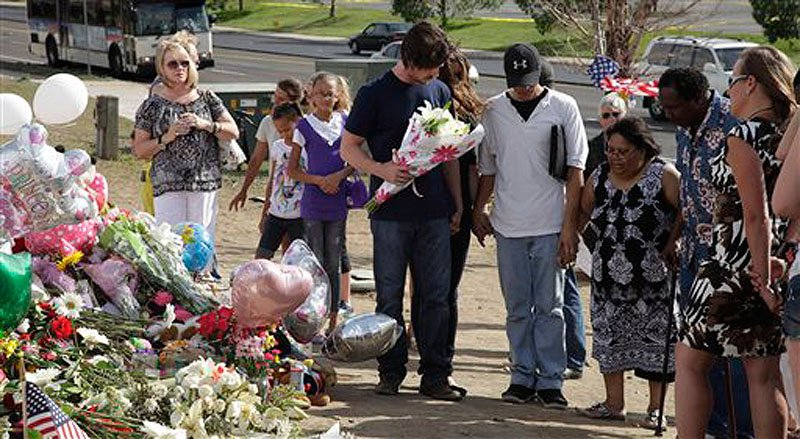 "Actor Christian Bale, holding flowers at center, joins hands and prays with visitors to a memorial to the victims of Friday's mass shooting, Tuesday, July 24, 2012, in Aurora, Colo. Twelve people were killed when a gunman opened fire during a late-night showing of the movie ""The Dark Knight Rises,"" which stars Bale as Batman. (AP Photo/Ted S. Warren)"
