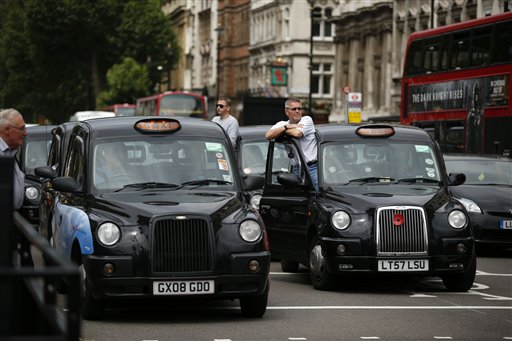London taxi drivers park their cabs on the junction of Whitehall and Parliament Square on Tuesday, as they take part in a protest to jam traffic in reaction to not being allowed to use the Olympic driving lanes in London.