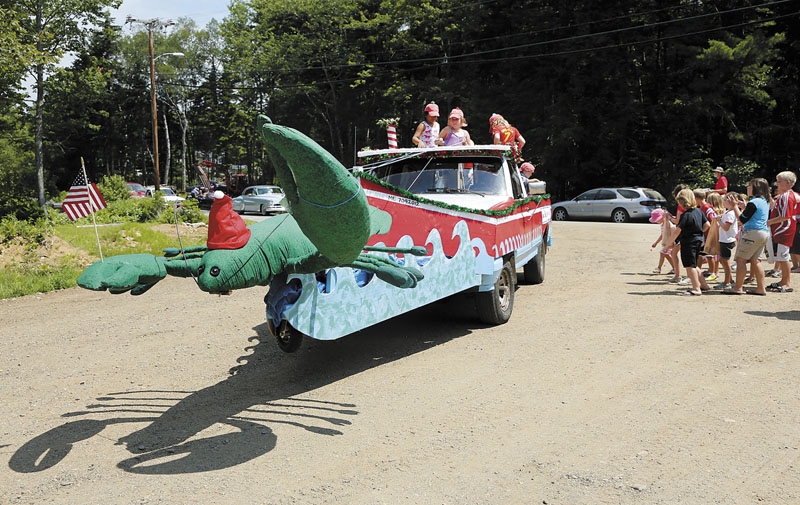 A truck decorated as a giant Christmas lobster is filled with children throwing candy and singing carols during the Chebeague Island Fourth of July parade.
