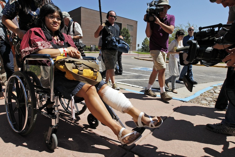 Rita Paulina, in wheelchair, who was injured in the attack, departs the Arapahoe County Courthouse after an arraignment hearing for accused theater shooter James Holmes, Monday, July 30, 2012 in Centennial, Colo. Colorado prosecutors filed formal charges Monday against Holmes, the former neuroscience student accused of killing 12 people and wounding 58 others at an Aurora movie theater. (AP Photo/Alex Brandon)