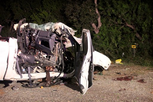 The wreckage of a pickup truck that authorities say was overloaded with passengers when it veered off a highway and crashed into trees near Goliad, Texas.