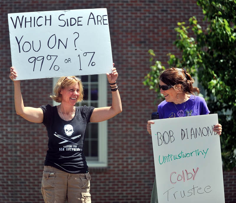 Kim Cormier, left, of Benton, and Lucia Robinson, of Whitefield, stand outside the Diamond Building at Colby College on Mayflower Hill Drive calling for chairman of the college's Board of Trustees Robert E. Diamond Jr. to resign and for Colby for remove him from their board and give back Diamond's donations.