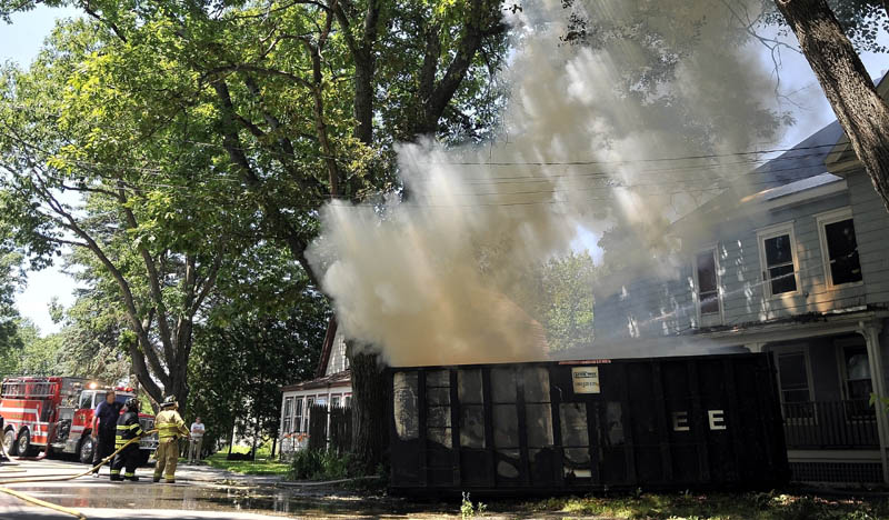 A firefighters from Winslow Fire Department battle a dumpster fire on Barton Street in Winslow Wednesday. The fire apparently started when a construction worker discarded a cigarette in the dumpster.